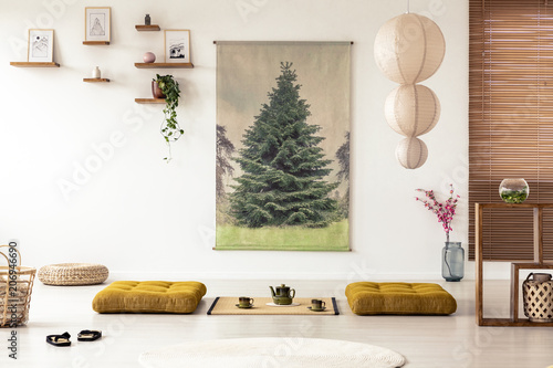 Japanese dining room interior with a tree poster, lamp, pillows and tatami mat with pot and cups on the floor - 206946690