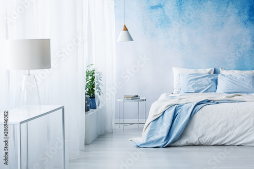 White lamp on a table in bright blue bedroom interior with bed against ombre wall