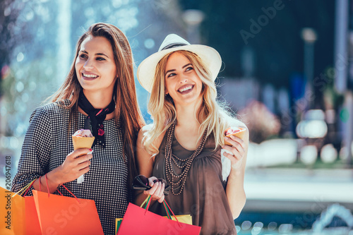 Leinwanddruck Bild Happy young women with shopping bags and ice cream having fun on city street