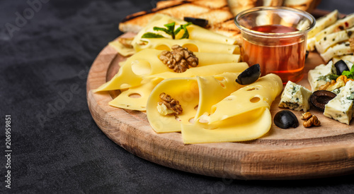 Fototapeta Cheese plate: Parmesan, cheddar, gouda, mozzarella and other with basil on wooden board on dark background with place for text.Honey and Crackers