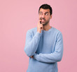 Handsome man having doubts and with confuse face expression on pink background