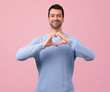 Leinwanddruck Bild - Man with blue sweater making heart symbol by hands. Being in love on pink background