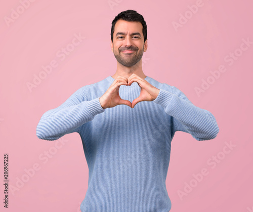 Leinwanddruck Bild Man with blue sweater making heart symbol by hands. Being in love on pink background
