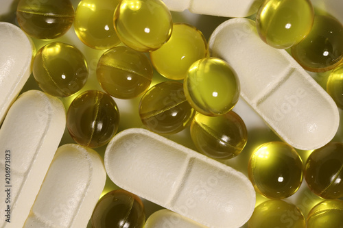 Fotobehang Apotheek White Medicine Tablets with Yellow Capsules. Pharmacy Pills Background. Macro Closeup. Top View.