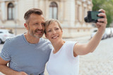 Middle-aged couple posing for a selfie in town - 206975206