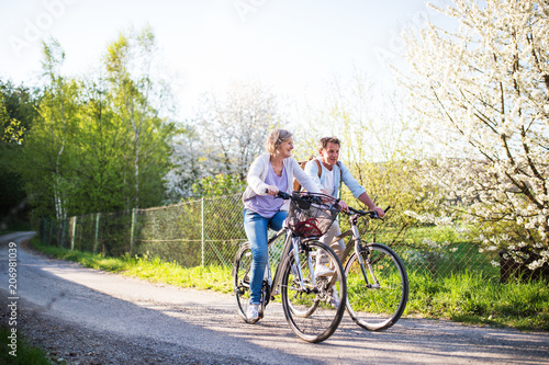 Leinwanddruck Bild Senior couple with bicycles outside in spring nature.