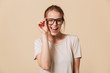 Leinwanddruck Bild - Portrait of beautiful cheerful woman 20s wearing basic t-shirt touching eyeglasses and smiling at camera while winking, isolated over beige background in studio