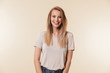 Image of beautiful pleased woman 20s wearing casual t-shirt laughing and looking at you with happy smile, isolated over beige background in studio