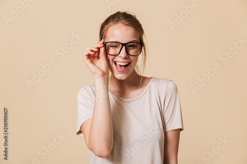 Leinwanddruck Bild Portrait of beautiful cheerful woman 20s wearing basic t-shirt touching eyeglasses and smiling at camera while winking, isolated over beige background in studio