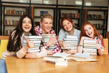 Group of cheerful teenagers sitting at the library table
