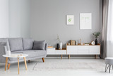 Grey settee near white cupboard in minimal living room interior with posters on the wall. Real photo - 207008810