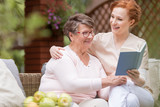 Cheerful senior woman with her tender caretaker reading a book together while relaxing outside. Close relationship. - 207008860