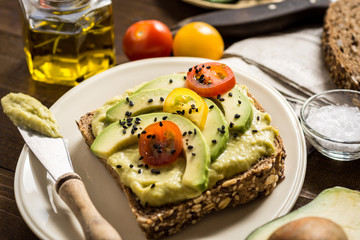 Avocado Spread Guacamole and Slices with Fresh Cherry Tomato and Black Sesame. Healthy Breakfast Concept.