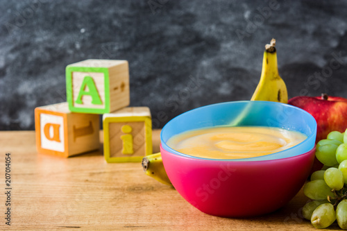 Baby food: colorful bowl of fruit puree on wooden table