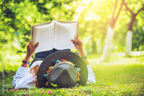 Fotobehang Zwavel geel Asian woman travel nature. Travel relax. sleep woman reading On the lawn in the park. in summer.