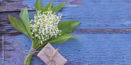 Fotobehang Lelietjes van dalen Bouquet of lilies of the valley and hand made gift box on old paint blue background with copy space