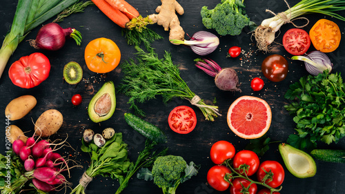 Healthy food. Vegetables and fruits. On a black wooden background. Top view. Copy space. - 207042444