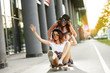 Two female friends playing with skateboard on street.One girl pushing other from behind.Laughing and fun.