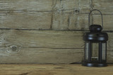 Black lantern on a background of old wooden boards. Abstraction. Concept. - 207046051