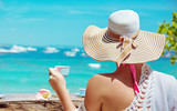 Young, relaxed lady drinking coffee in a beach bar - 207050240