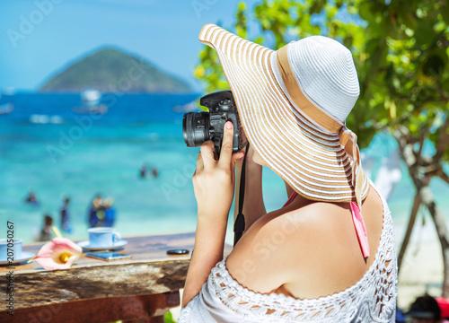 Fotobehang Konrad B. Relaxed, joyful lady taking a photo of a tropical beach
