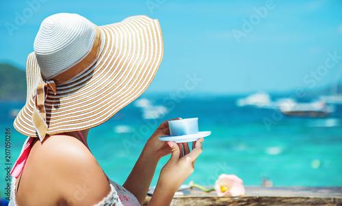 Fotobehang Konrad B. Elegant lady drinking coffee on a beach