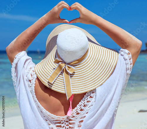Fotobehang Konrad B. Young lady making a heart gesture on a beach