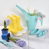 Yellow rubber boots and blue watering can with a bouquet of flowers of yellow daffodils and white and pink tulips on the white background. Garden accessories. - 207055422
