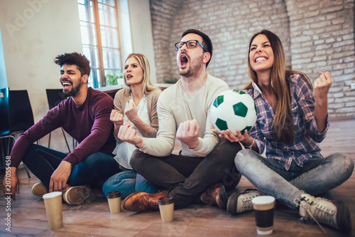 Fotobehang Voetbal Happy friends or football fans watching soccer on tv and celebrating victory. Friendship, sports and entertainment concept.