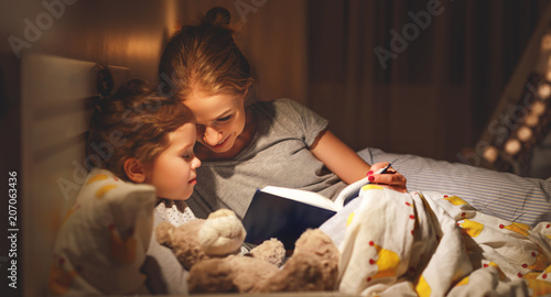 Leinwanddruck Bild mother and child reading book in bed before going to sleep .