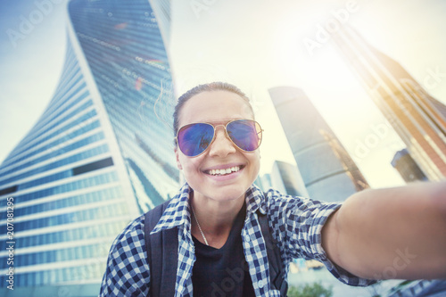 Fotobehang Moskou Beautiful young woman girl doing selfie on a smartphone on the background of the business center of Moscow City, traveling to Russia