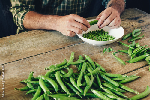 Male hands clean green peas sitting wooden table kitchen close up Rustic style Green peas bowl wooden table