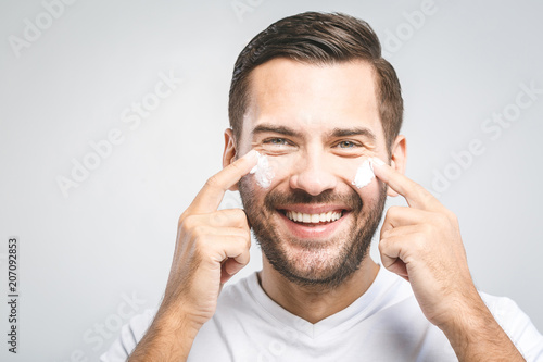 Foto Murales Skin care. Handsome young shirtless man applying cream at his face and looking at himself with smile while standing over gray background and looking at camera. Close-Up. Space for text.