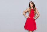 Smiling Young Woman In Elegant Red Dress Is Looking Away - 207101611