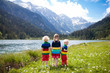 Leinwanddruck Bild - Children hiking in flower field at mountain lake