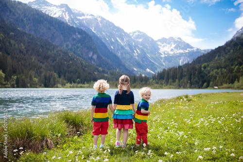 Leinwanddruck Bild Children hiking in flower field at mountain lake