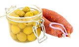 Glass storage jar filled with green olives next to a whole chorizo salami isolated on a white background