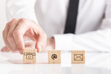 Businessman placing cubes with email and phone pictograms