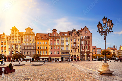 Zdjęcia na płótnie, fototapety na wymiar, obrazy na ścianę : Central market square in Wroclaw Poland with old colourful houses, street lantern lamp and walking tourists people at gorgeous stunning morning sunrise sunshine. Travel vacation concept