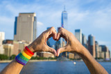 Hands wearing gay pride rainbow sweat band making heart symbol in front of city skyline
