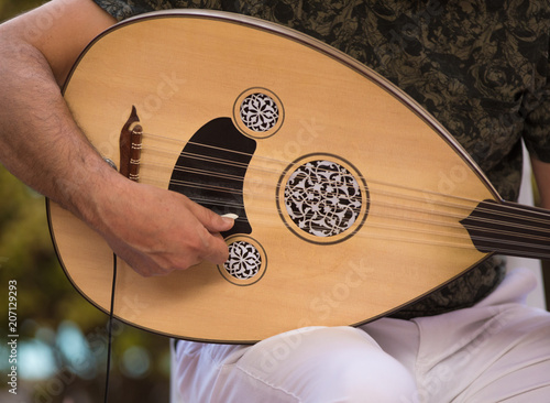 playing an Arabic stringed musical instrument - 207129293