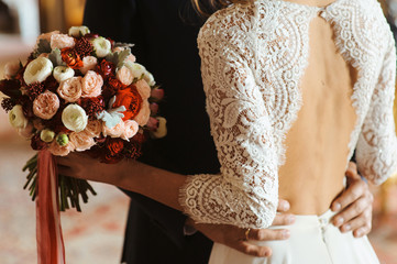 Hands of groom and bride at wedding day. Bridal couple hugging. Wedding bouquet at background. Wedding love and family concept close up macro photo with selective focus