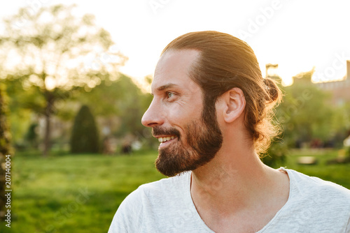 Profile portrait closeup of stylish bearded man 30s with tied hair in white t-shirt smiling, while walking in green park
