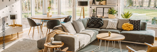 Side angle of a corner sofa with pillows, table and dining table with chairs behind in a bright living room interior - 207143071