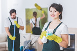Group of young, hard-working professional cleaners in dirty apartment. Woman with cleaning solution and cloth against blurred background - 207143225