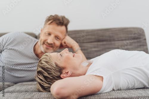 Leinwanddruck Bild Woman lying on her back relaxing on a sofa