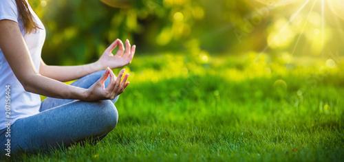 Wall mural Yoga woman meditating at sunset