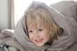 Petit garçon se cache sous la couverture