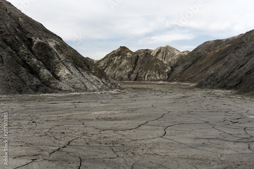 Aluminium Grijs landscape - view from the bottom of a dry desert canyon with a sandy-clay bottom and weathered slopes