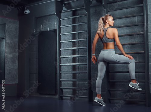 Seksowna sportive kobieta robi rozciąganiu opiera na ściennych barach w nowożytnym sprawności fizycznej centrum.
